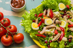 Salad with mushrooms, chicken, quail eggs, paprika, lettuce and pomegranate, on a old table. Top view Stock Photos