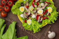 Salad with mushrooms, chicken, quail eggs, paprika, lettuce and pomegranate, on a wooden table. Top view Royalty Free Stock Photos