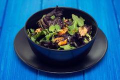 Salad with mussels in black bowl Royalty Free Stock Images