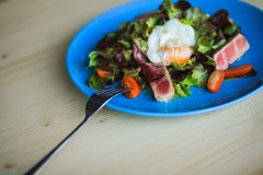 Salad Nicoise on a blue plate with poached egg. Salad Nicoise with tuna fish, boiled eggs, tomatoes, iceberg Stock Photo