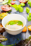 Salad oil dressing with tomatoes and basil on blue rustic background Royalty Free Stock Images