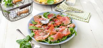 Salad with parma ham jamon , tomatoes and arugula on the plate. stock photo