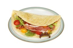 Piada on a plate. Salad and parma ham piada on a plate isolated against white Royalty Free Stock Photography