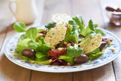Salad with parmesan chips, dried tomatoes and olives Royalty Free Stock Photography