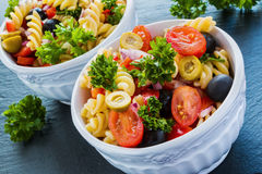 Salad: pasta fusilli, black and green olives, cherry tomatoes, red onion and parsley. Dressing: olive oil and lemon juice. In white bowl. Black stone Stock Photography