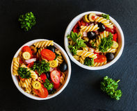 Salad: pasta fusilli, black and green olives, cherry tomatoes, red onion and parsley Royalty Free Stock Photos