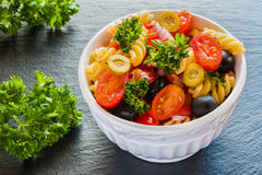 Salad: pasta fusilli, black and green olives, cherry tomatoes, red onion and parsley Royalty Free Stock Images