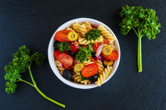 Salad: pasta fusilli, black and green olives, cherry tomatoes, red onion and parsley Stock Images