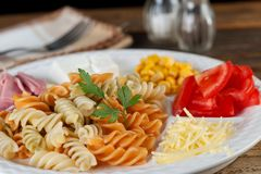 Salad of pasta fusilli with tomatoes corn cheese and ham on wooden background Stock Images