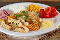 Salad of pasta fusilli with tomatoes corn cheese and ham on wooden background Royalty Free Stock Images