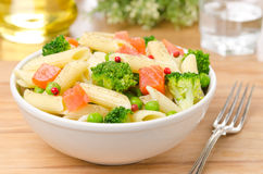Salad with pasta, salmon, broccoli and green peas on wooden table Royalty Free Stock Image