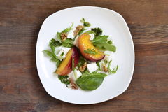 Salad with peaches, arugula, cream cheese, pesto and walnuts Royalty Free Stock Images