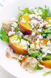 Salad with peaches, bacon; arugula, spinach and goat cheese Royalty Free Stock Photo