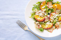Salad with peaches, bacon; arugula, spinach and goat cheese Stock Image