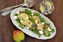 Salad with pears, arugula, cream cheese and walnuts Royalty Free Stock Images