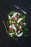 Salad with pears, baby spinach, figs, walnuts, goat cheese and honey on black stone background Stock Photo