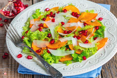 Salad with persimmon and pomegranate seeds close-up. Stock Images
