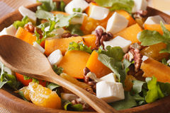 Salad with persimmons, walnuts, arugula, cheese and oranges macr. Healthy salad with persimmons, walnuts, arugula, cheese and oranges macro. horizontal stock images