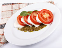 Salad with pesto sauce. Fresh salad from tomatoes with cheese a mozzarella and pesto sautse Royalty Free Stock Photo