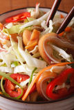 Salad with pig ears and vegetables in a bowl macro. vertical Stock Image