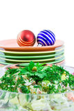 Salad, plates and new years's baubles. Salad olivie against pile of plates with new years's baubles Stock Images