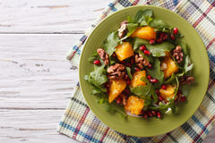 Salad with pomegranate, oranges, arugula and nuts. horizontal to. Delicious salad with pomegranate, oranges, walnuts and arugula on the table. horizontal top stock image