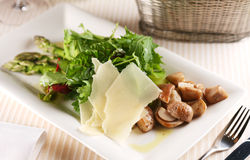 Salad with porcini mushrooms and arugula. On a white plate Royalty Free Stock Images