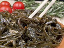 Salad from porsky cabbage. Bamboo chopsticks in salad from sea cabbage stock photo