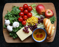 Salad preparation on choppig board. Variety of fruit salad bread cheese and olive oil Mediterranean diet Stock Photo