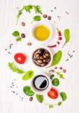 Salad preparation with dressings,olives, wild herbs leaves, chili, oil and tomatoes. On white wooden background, top view royalty free stock photography