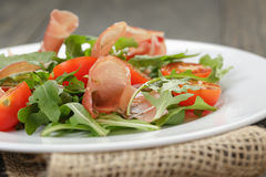 Salad with prosciutto arugula and tomatoes Royalty Free Stock Photography