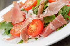 Salad with prosciutto arugula and tomatoes Stock Photography