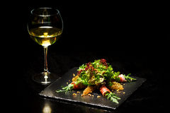 Salad with prosciutto and glass of wine. royalty free stock photos