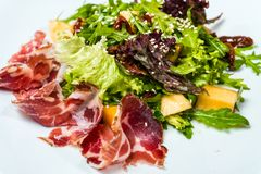Salad with prosciutto and mango in a white plate royalty free stock photo