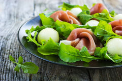 Salad with prosciutto, melon and arugula Royalty Free Stock Images