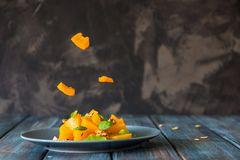 Salad with pumpkin, walnuts and green leaves, levitation ingredi. Ents Royalty Free Stock Photos