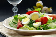 Salad with quail eggs and arugula on beige plate Royalty Free Stock Photo