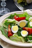 Salad with quail eggs and arugula on beige plate Royalty Free Stock Photography