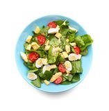 Salad with quail eggs and spinach in plate isolated. On white Royalty Free Stock Image