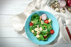 Salad with quail eggs and spinach in plate. On table Stock Photos