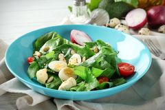 Salad with quail eggs and spinach in plate. On table Stock Images