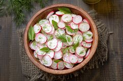 Salad with radish and herbs. In wooden bowl, top view Royalty Free Stock Photo