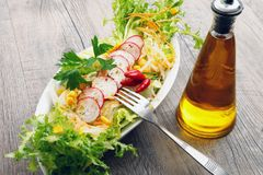 Salad with radish and mais on wooden table royalty free stock image