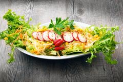 Salad with radish and mais on wooden table Stock Photography