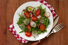 Salad with radish on plate. On brown background Stock Photo