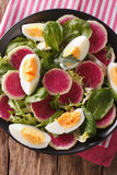 Salad with radishes, eggs, spinach and lettuce mix close-up. ver. Salad with radishes, eggs, spinach and lettuce mix close-up on the table. vertical view from Royalty Free Stock Photo