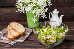 Salad with radishes, lettuce, spinach and olive oil on a wooden table. Close-up Royalty Free Stock Photography
