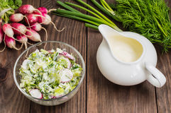 Salad with radishes, lettuce, spinach and sour cream on a wooden table. Close-up. Salad with radishes, lettuce, spinach and sour cream on a wooden table Royalty Free Stock Photo