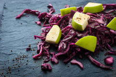 Salad of red cabbage and apples on the dark stone horizontal Royalty Free Stock Image