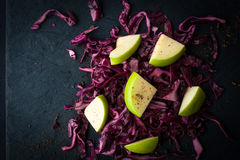 Salad of red cabbage and apples on the dark stone top view Stock Photos